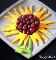 Een zonnebloem van druiven, meloen of mango en een bleekselderijstengel.