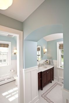 Traditional bathroom with dark wood vanity, white wainscoting, and light blue walls