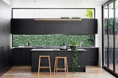 Elsternwick renovation. Clean lines and dark tones define the new minimalist kitchen. The low level splash back window frames the landscaped corridor beyond and full height doors fold to extend the open plan space. Built by SVS Projects ; Photography by @gemmola ; Styling by @ruthwelsby ; stools by @tide_design ; ceramics by @cone11ceramics & @forkceramics #buildingdesign #renovation #extension #kitchendesign #melbourne