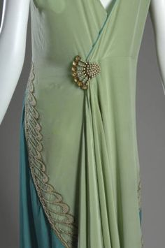 1928. Dress of light green silk charmeuse with blue green side panels. V-shaped neckline front and back; sleeveless; hem falls to knee in front, and to the ankles in back. Pearl and metallic thread embroidery form a wing pattern across chest, and an uneven scallop pattern on the skirt. Back features a fan-shaped brooch made of pearls and glass beads.