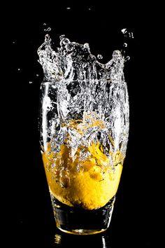 Lemon falling into a glass of water