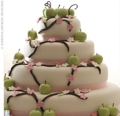 cute!  Green fondant apples and flowering branches cascaded down the four-tiered, white cake, which was lined with pink ribbon.