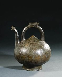 A SAFAVID BRONZE KETTLE  PERSIA, LATE 16TH CENTURY  Of onion form on short trumpet foot with loop handle & straight spout terminating in dragon's head finial, body engraved with a row of cartouches containing animals & paired birds, one with nasta'liq inscription divided by lozenge-shaped cartouches containing arabesques issuing further medallions containing animals, a band of engraved palmettes on the shoulder, handle with hinged opening for filling above, slightly rubbed, dark brown patina