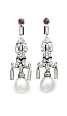 A PAIR OF ART DECO NATURAL PEARL, DIAMOND AND MULTI-GEM EAR PENDANTS, BY CARTIER: Each suspending a slightly baroque drop-shaped natural pearl, from a single-cut diamond and calibré-cut onyx pagoda-shaped plaque, suspending variously-cut diamonds trimmed with black enamel, to the cabochon ruby surmount, circa 1925, 2 1/4 ins., with French assay marks for platinum. Signed Cartier, no. 0365. Via Christie's.