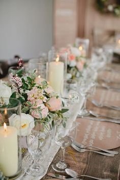 Blush pink flowers and big candles as table centerpieces