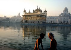Two young devotees preparing to take a dip and the Holy Amrit Sarovar, Harmandir Sahab, Amritsar.