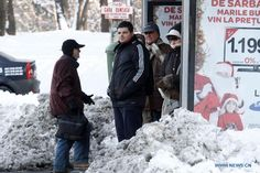 Citizens wait for bus on a snow-covered street in Bucharest, capital of Romania, Dec 13, 2012. Most of the trains were delayed and many others suspended as heavy snow and cold hit Romania on Thursday.