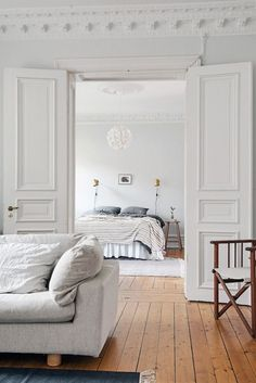 wood and pale furnishings. Brass wall lamps around bed.