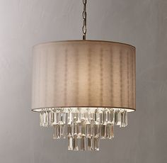 RH TEEN's Raina Crystal Pendant:A study in contrasts. A simple linen drum shade pairs with cascading crystal drops – juxtaposing opulent elegance with clean-lined forms. Faceted crystals hang from beneath the shade for extra sparkle when illuminated.