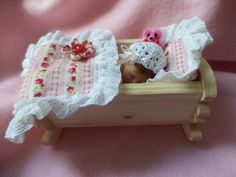 Minature polymer clay baby girl in wooden crib with Layette and teeny tiny teddy