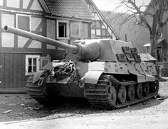 A (SdKfz 186) Jagdtiger tank hunter shows its massive profile while resting next to this 2 story building