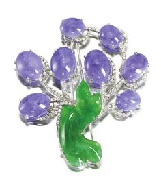 A lavender jadeite, jadeite and diamond brooch Designed as a tree, set with lavender oval jadeite cabochons of very good translucency, the branches set with brilliant-cut diamonds, to a bright green jadeite of good translucency, carved as a tree trunk, mounted in 18k white gold.