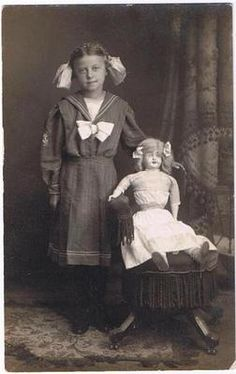 Girl In A Sailor Dress With A Doll 1912
