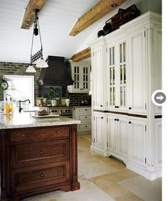 Antiqued white cabinets, travertine floor tiles and a commercial-grade stove.The range hood was made from recycled wood. Brick veneer was used as a backsplash.