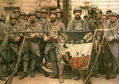 French infantry poses with his torn flag after the battle, July 14, 1917.
