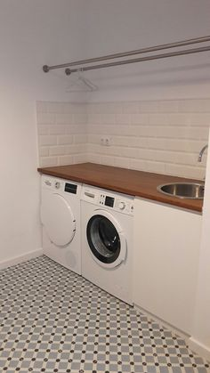 Lovely and clean laundry room with white subway tiles, wooden countertop and pattern ceramic floor tiles