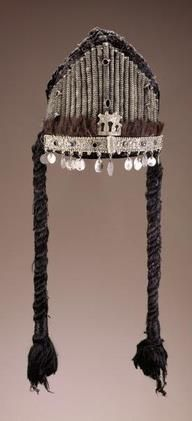 Morocco | Headress. Early 20th century | Cotton cloth, silver alloy, glass, stone, animal hair, fiber | A headdress helped a Moroccan Jewish woman to conceal her hair after marriage and proclaim her pride in her heritage. Headdresses from the Drâ valley have a rigid peaked structure covered with cotton velvet. Tubes of coiled silver adorn the upper front portion, while a fringe of cattle or goat hair borders a decorative silver band.