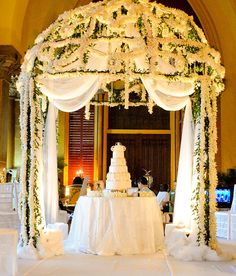 Boca By Design. A large circular arch with white and green hanging floral to make the cake pop!