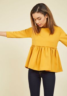 Do you love a fluttering hem, a subtle hint of femininity, and stylish sweetness? Then, this golden top - arriving this October - is a must-have! The exposed, ruffled seam of this 3/4-sleeved blouse only adds to its charm, making this woven peplum the best of its kind.