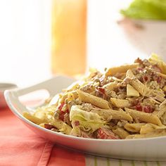 Bacon Cheeseburger Pasta Salad -  1-1/2 cups mayonnaise 1/4 cup, plus 2 Tbsp, ketchup 1/4 cup, plus 2 Tbsp, yellow mustard 1/2 cup, plus 2 Tbsp, dill pickle relish 2 tsp black pepper 1 lb penne pasta, cooked and cooled 1-1/4 lbs ground beef, cooked, drained, and cooled 3/4 lb bacon, cooked until crisp, drained, cooled, and diced 3/4 cup red onion, small dice 10 slices American cheese, medium dice 6 cups iceberg lettuce, large dice 3 cups cherry tomatoes, halved