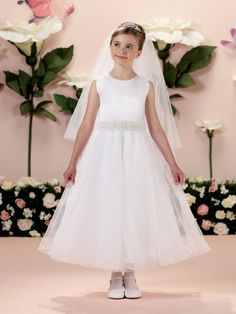Sleeveless satin and tulle tea-length A-line dress with jewel neckline, satin bodice features a wide hand-beaded waistband, covered buttons down back, full tulle overlay circle skirt, ideal for First Holy Communion. Sizes: 6 – 14, 8 ½ – 14 ½