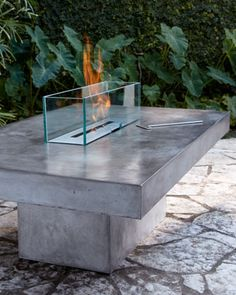 "Outdoor Firepit at Horchow. Table and base handcrafted of low-lustre polished concrete; imported. Glass guard made in the USA of heat-strengthened glass. Uses bio-fuel (not included). 62""W x 40.5""D x 32""T."