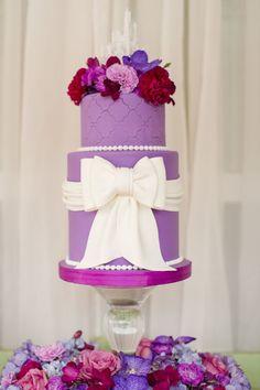 Pastel de bodas en orquidea radiante con lazo blanco y detalle floral de Fairytale Floral - Foto de Katelyn James