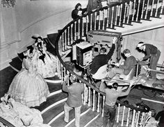 Marcella Martin as Cathleen Calvert on staircase at Twelve Oaks, talking to Vivien Leigh as Scarlett O'Hara. Director Victor Fleming stands on stairs back to camera. Technicians, crew, and extras surround. the Making Film 'Gone With the Wind,' 1939