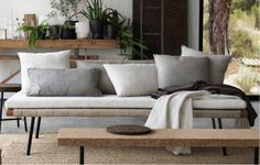 {color palette : neutrals--whites, greys, beige, with green and lightness from glass and thin legged furniture}デイベッドの上に白、グレー、白黒のストライプ模様のクッションが置かれています。