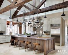 An open cooking space allows family and guests to chat and prepare meals together in the kitchen. The island, which was distressed and stained by Evco Painting, is paired with wooden stools by Theodore Alexander, purchased at Stockton Hicks Laffey. Two Hills Studio fabricated the pot hanger; its shades and pendants are from Northeast Lantern.