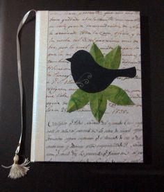 Cuaderno para firmas, forrado con papel y decorado con pájaro de cartulina negra y hojas de papel verde