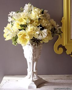 Give a gentle nod to the season with this fresh take on a pastel Easter palette. Fragrant white hyacinths and buttery-yellow double tulips and carnations shimmer against green-and-white pittosporum foliage. A porcelain vase sets off the textures and tones of the flowers, as well as the variegated leaves. We began by grouping stems of pittosporum to shape a framework and establish height. The rest was filled in with hyacinths, then tulips and carnations, to create a mounded form