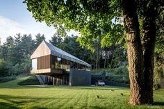 toit mansardé, bardage bois vertical, baies vitrées,et garage moderne d'une maison d'architecte