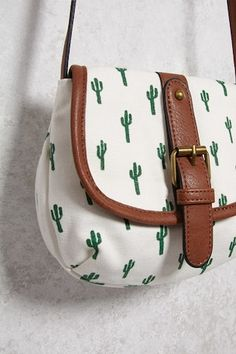 $12.90 |  A canvas crossbody bag featuring an allover cactus print, an adjustable faux leather shoulder strap, a burnished buckle, and a flap-top with a magnetic snap-button closure.