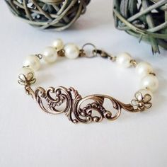 "Sweet Lace Bracelet - Brass Ivory  A detailed floral filigree branch, curved to fit the wrist, shines beautifully as the centerpiece of this bracelet. The antiqued brass embellishment has a smooth finish and darling floral twists, and paired up with ivory pearls, the 2"" branch is elegant and sophisticated. Sweet Lace bracelet measures 7"" with an additional 1.5"" extender. If you need a different size or different colored accent beads, please convo me and I'll customize it for you.  $19.00"