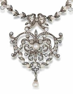 A late 19th century pearl and diamond necklace. Set throughout with cushion-shaped, old brilliant, brilliant, rose and single-cut diamonds and pearls, the scrolling openwork cartouche surmounted by a ribbon-bow motif and suspending a pearl drop, on a foliate knifewire chain interspersed with pearls, mounted in silver and gold, diamonds approximately 7.25 carats total.