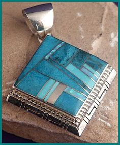 """This square pendant is mounted on point. Inlayed with Sunnyside Turquoise from Nevada, Sleeping Beauty Turquoise from Arizona and cultured opal. Pendant is approximately 1- 1/4"""" inches square. Bottom 2 sides are hand sawn. Inlay by Navajo artist Larry Chavez Offered at $559.00 Share the post """"Silver, Turquoise and Opal Pendant 55"""" FacebookTwitterGoogle+PinterestLinkedInE-mail"""