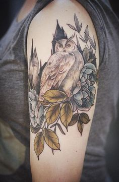 A Harry Potter inspired sleeve tattoo. The owl symbolizes a character from the book as it perches on a group of blue roses. Behind the owl is what we can all guess as Hogwarts School of witchcraft and wizardry.