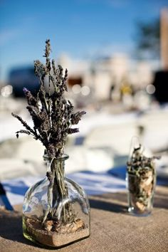 "Great use of empty patron bottles.  ""cheap"" center pieces with sand, rocks and twigs? Maybe with a mason jar instead?"