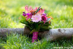 Mooi kleurrijk bruidsboeket met een roze lint om de stelen van de bloemen.  http://www.rikkemienfotografie.nl/