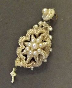"""Early 19C --- A seed pearl pendant, with 10 larger pearls (possible an earring) ---  This is interesting, because it's clearly coming apart, so we can see a bit of how it was made.  The mount is a frame of ivory or bone, pierced so that the seed pearls could be """"embroidered"""" onto it."""