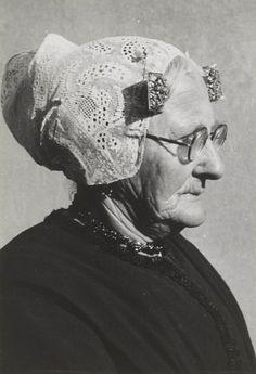 Mevrouw Kuijt in streekdracht uit Katwijk. Ze is gekleed in zondagse dracht. Ze draagt over de ondermuts het zilveren oorijzer met aan de uieinden rechthoekige gouden 'boeken', versierd met cantillewerk. Over het oorijzer draagt ze een hul (muts), met fijngeplooide voorstrook en opgespelde punten. Achter de boeken is een paar mutsenspelden met een parel in de muts gestoken. Mevrouw Kuijt draagt een jak, rok en schort en ze heeft een schoudermantel omgeslagen. 1943 #ZuidHolland #Katwijk