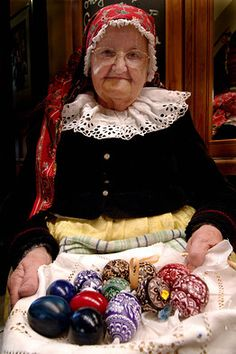 A Czech woman in traditional costume showing her hand-painted Easter eggs