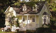 Playhouse? Um, I want to live here. - A cottage with white picket fences, this small home sits among lush landscaping and features a garlanded trellis leading to the front porch. It measures 12 feet by 14 feet by 11 feet.