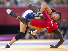 Canada 's Carol Huynh takes down Isabelle Sambou of Senegal to win the Bronze medal match in 48kg Women's Freestyle Wrestling at the Olympic Games.