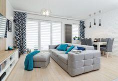 aménagement salon salle à manger - canapé et table basse gris clair au centre de la pièce, mur de brique blanche et chaises tapissées grises