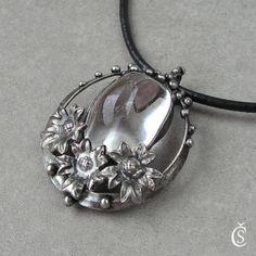 """Kvetoucí Máj - Křišťál Autorský náhrdelník """"Kvetoucí Máj - Křišťál"""" ...je vyroben z bezolovnatého cínu a Křišťálu. Kámen je čirý a hladký s maličkými povrchovými inkluzemi. Náhrdelník je patinován, leštěn, broušen a povrchově ošetřen. Rozměry šperku jsou šířka 4 cm x výška cca 5,5 cm. Součástí šperku je černá kulatá kůže v délce 45 cm. Na ..."""