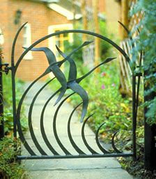 modern metal garden gate with flying birds for english cottage