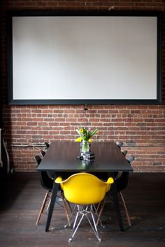 """""""It was designed as a conference room with a media projector for meetings with partners and some of our remote team members, says Lucas. We added white drop curtains to the dividing glass wall for optional privacy, which also allows the glass wall to double as more white board space (we white board a lot!)."""""""