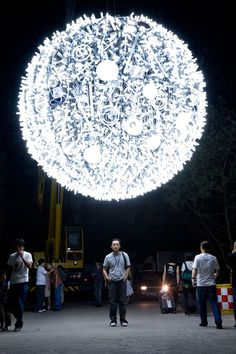 Artist Wang Yuyang recreates a lunar presence with his work, Artificial Moon, made from hundreds of CFL bulbs, spanning 13 feet in diameter, and suspended floating between trees.